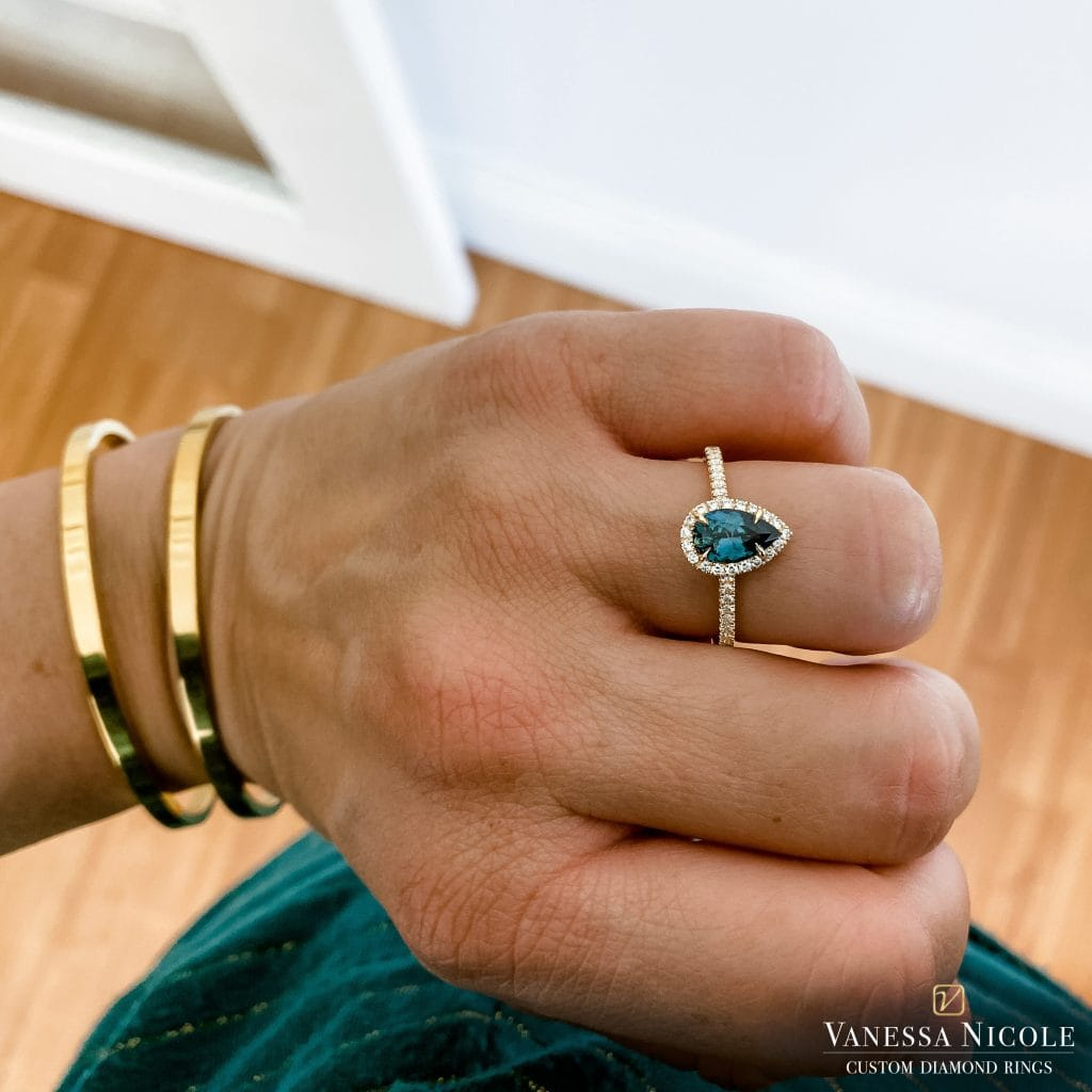 pear shaped emerald stone in halo micro pave platinum eternity band setting